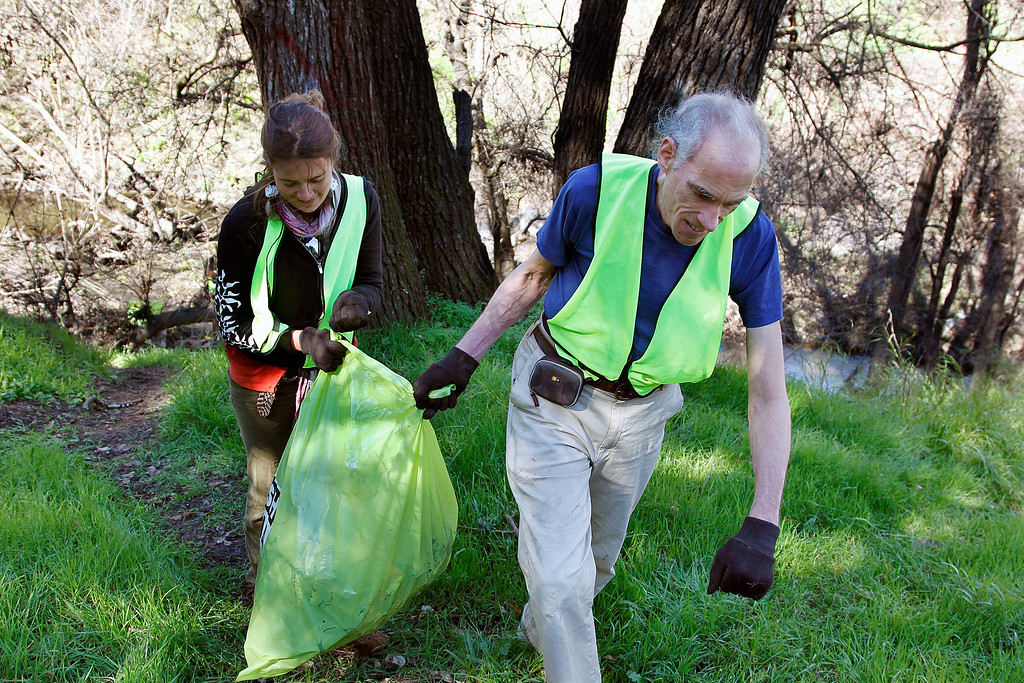 . Richard Gehrs, right, and Rachel Kippen of Save Our Shores, carry bags of trash out of Coyote Creek during a clean-up near the Highway 280 overpass and Selma Olinder Park, in San Jose, Calif. on Saturday, Feb. 9, 2013.   (LiPo Ching/Staff)