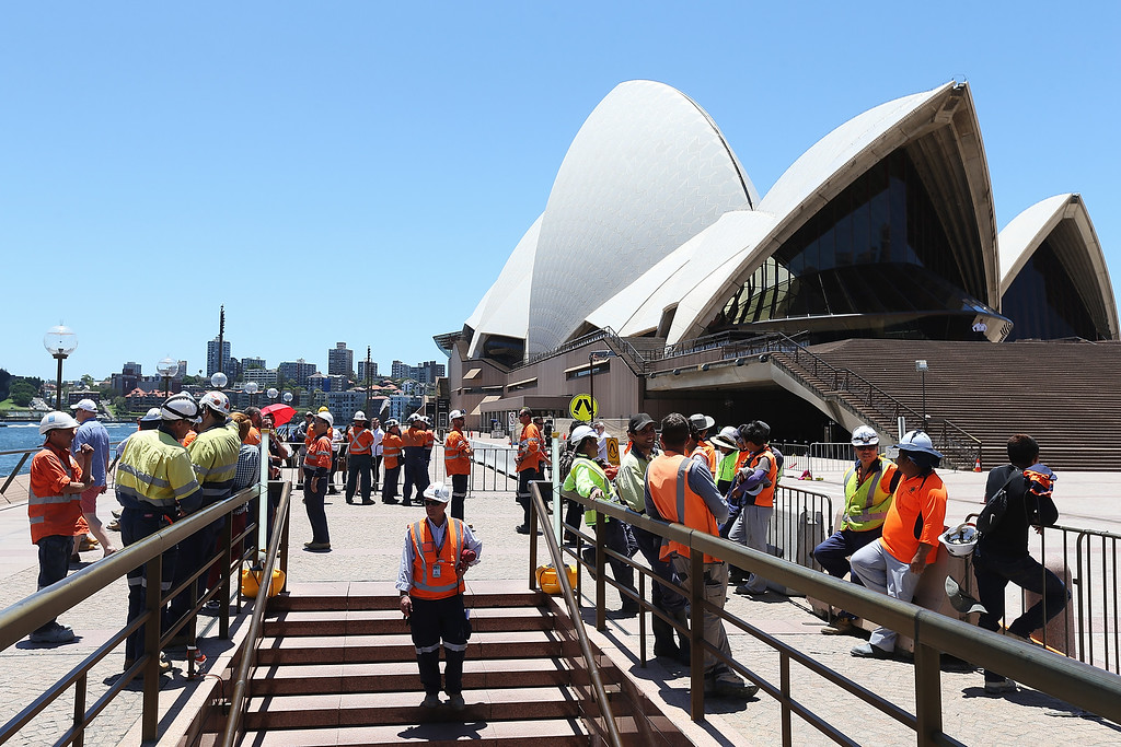 . SYDNEY, AUSTRALIA - DECEMBER 15:  Constraction workers gather in front of the Sydney Opera House after being evacuated on December 15, 2014 in Sydney, Australia.  Major landmarks in Sydney, including the Sydeny Opera House, have been evacuated as police respond to a hostage situation inside a Martin Place cafe. An armed man believed to be an Islamic terrorist is holding at least 20 people hostage at Lindt Chocolate Café. (Photo by Joosep Martinson/Getty Images)