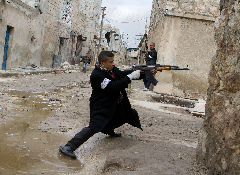 . A Syrian rebel aims his weapon during clashes with government forces in the streets near Aleppo international airport in northern Syria on March 4, 2013. Syria is locked in a nearly two-year-old conflict in which the United Nations estimates that more than 70,000 people have been killed.  STEPHEN J. BOITANO/AFP/Getty Images