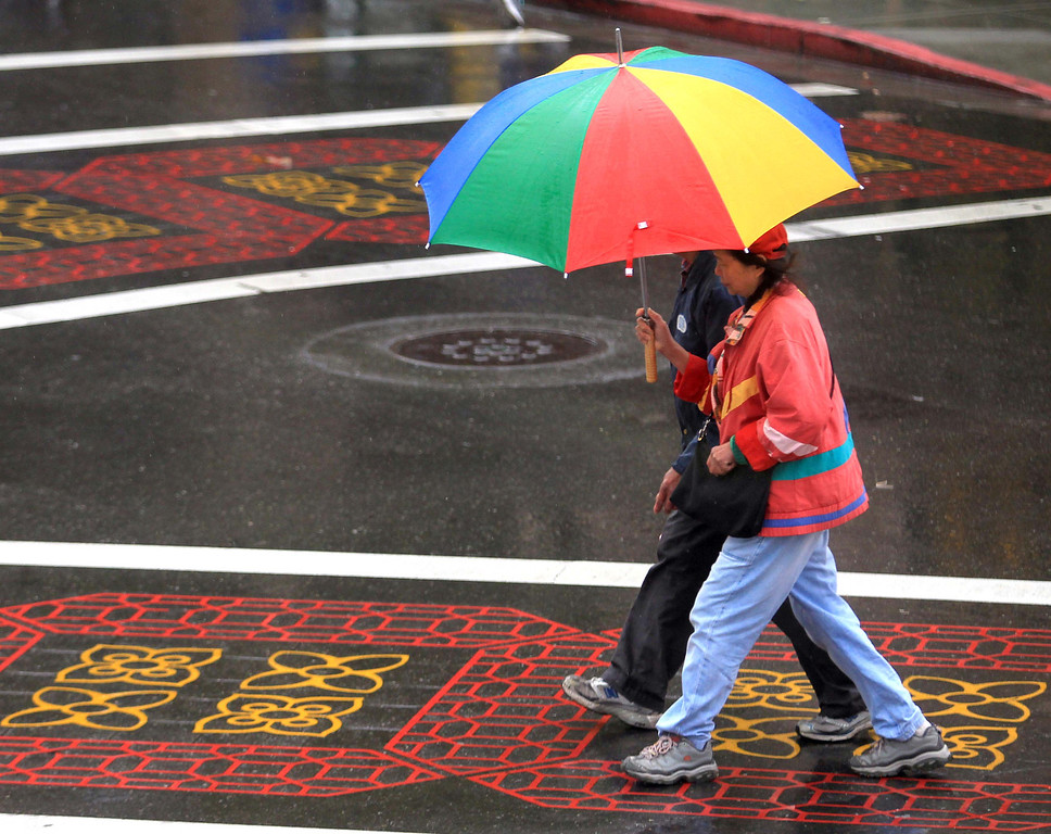 . Pedestrians make their way through the rain on Webster and 9th Streets in Chinatown in Oakland, Calif., on Tuesday, Feb. 19, 2013. Skies are expected to clear on Wednesday. (Jane Tyska/Staff)