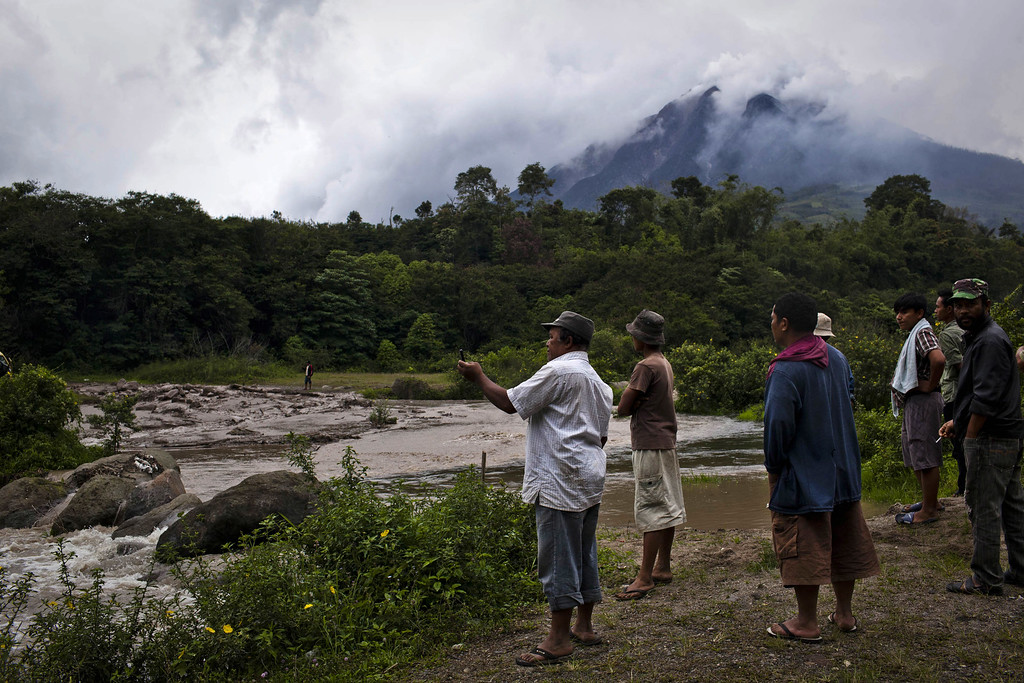 . Villagers watching cold lava flow from mount Sinabung in Gamber village on November 15, 2013 in Karo district, South Sumatra, Indonesia.   (Photo by Ulet Ifansasti/Getty Images)