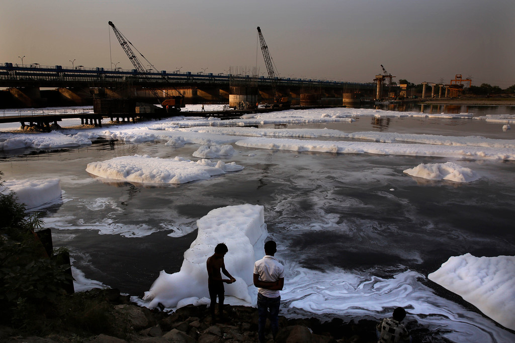. An Indian man dresses after bathing amidst industrial effluence in the river Yamuna on Earth Day in New Delhi, India, Tuesday, April 22, 2014. (AP Photo /Manish Swarup)