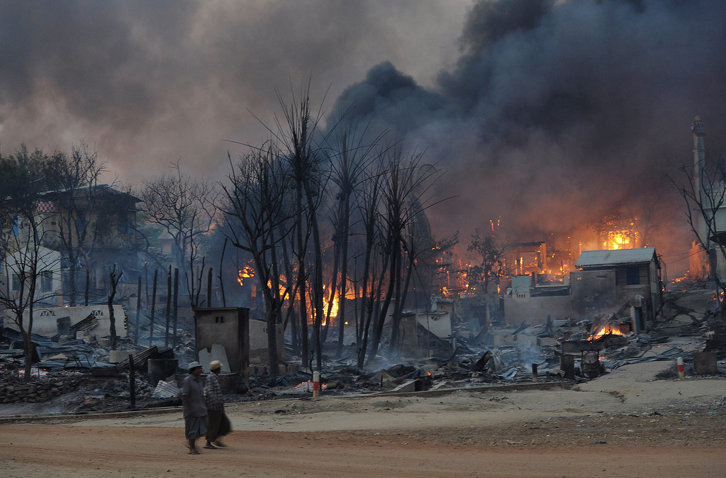 . Residents walk past buildings burning in riot-hit Meiktila, central Myanmar, on March 21, 2013.    Than WIN/AFP/Getty Images