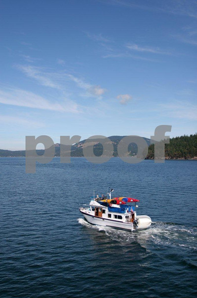 A powerboat loaded with kayaks finds its way through the San Juan Islands.
