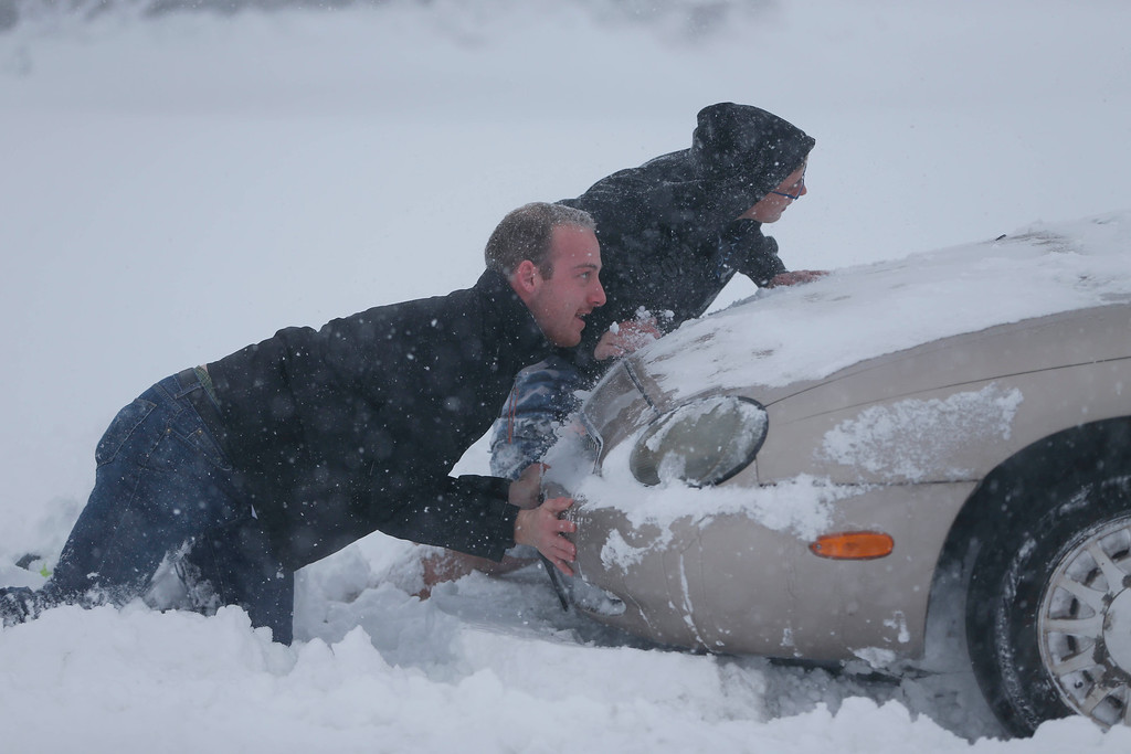 . Eric Dehond, left, and Dakota Paciorkowski help push out a stuck motorist on George Urban Boulevard in Depew, N.Y. on Tuesday, Nov. 18, 2014.  Several feet of lake-effect snow paralyzed the Buffalo area Tuesday, forcing state troopers to deliver blankets and other supplies to motorists stranded on the New York State Thruway and adding an ominous note to a wintry season that\'s already snarling travel and numbing fingers from the Midwest to the Carolinas.  (AP Photo/The Buffalo News, Derek Gee)
