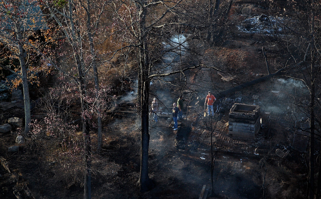. People survey a destroyed building as it sits among burned trees Tuesday, Nov. 29, 2016, near Gatlinburg, Tenn., after a wildfire swept through the area Monday. (AP Photo/Wade Payne)