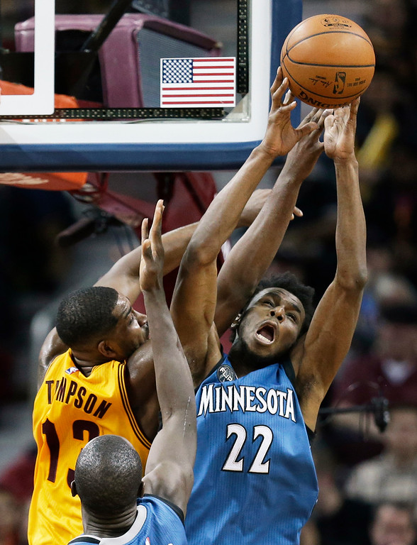 . Minnesota Timberwolves\' Andrew Wiggins (22), from Canada, and Cleveland Cavaliers\' Tristan Thompson (13), from Canada, battle for a rebound in the second half of an NBA basketball game Monday, Jan. 25, 2016, in Cleveland. The Cavaliers won 114-107. (AP Photo/Tony Dejak)