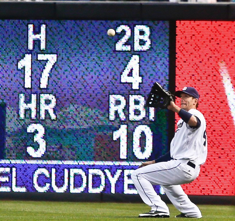 . San Diego Padres right fielder Chris Denorfia squats down to catch a line drive hit by Colorado Rockies\' Michael Cuddyer  in the first inning of a baseball game Tuesday, April 15, 2014, in San Diego. (AP Photo/Lenny Ignelzi)