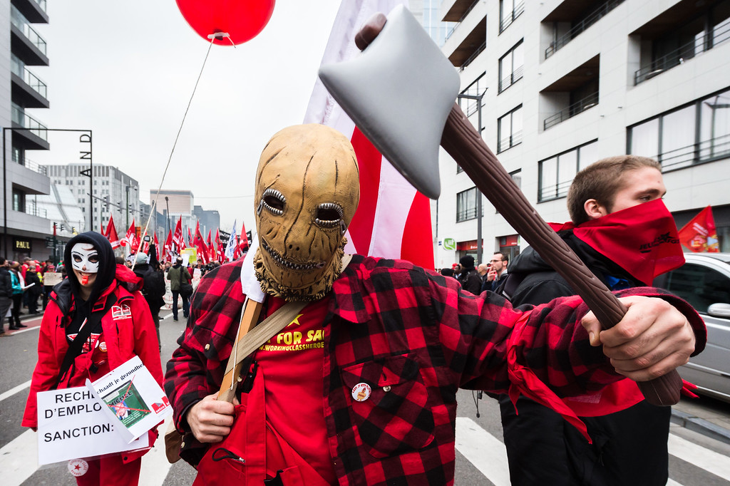 . A worker holds a fake axe during a national trade union demonstration in Brussels, Thursday Nov. 6, 2014. Tens of thousands of demonstrators are converging on the Belgian capital to protest government policies that will extend the pension age, contain wages and cut into public services.(AP Photo/Geert Vanden Wijngaert)