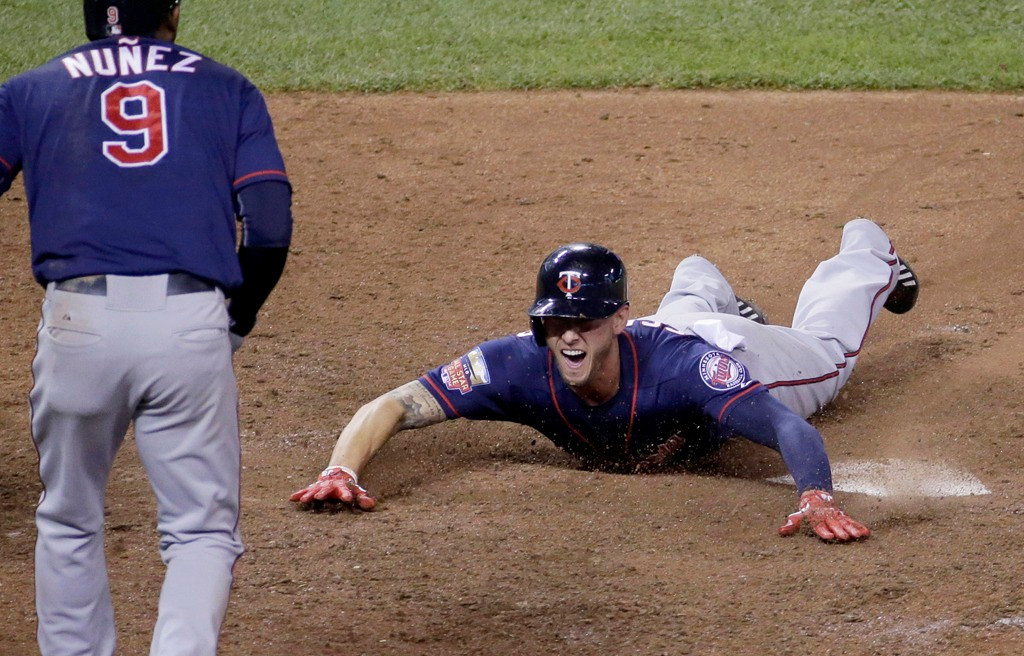 . Minnesota\'s Jordan Schafer hollers after he and Eduardo Nunez, left, scored on a double by Brian Dozier during the Twins\' six-run rally in the 10th inning to beat the Royals 11-5 on Thursday, Aug. 28, 2014, in Kansas City, Mo.  (AP Photo/Charlie Riedel)