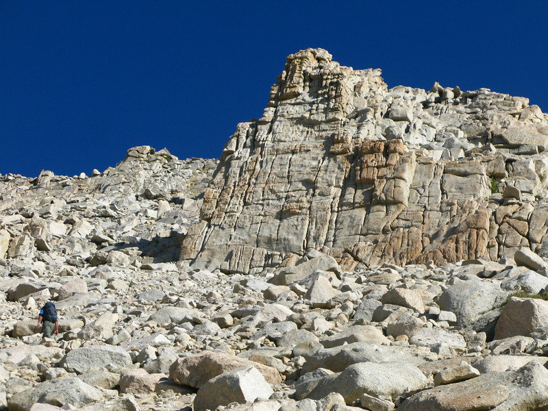 stay on the scree and pass under this rock wall