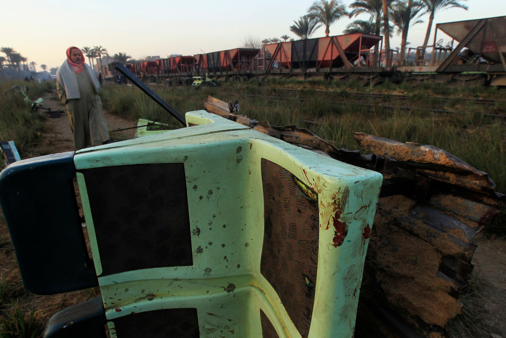 Description of . The wreckage of a military train crash is pictured  in the Giza neighbourhood of Badrashin, about 40 km (25 miles) west of Cairo, January 15, 2013. A military train carrying young recruits to an army camp derailed in a Cairo suburb on Tuesday, killing 19 people and injuring 107, Egypt's health ministry spokesman said.   REUTERS/Mohamed Abd El Ghany