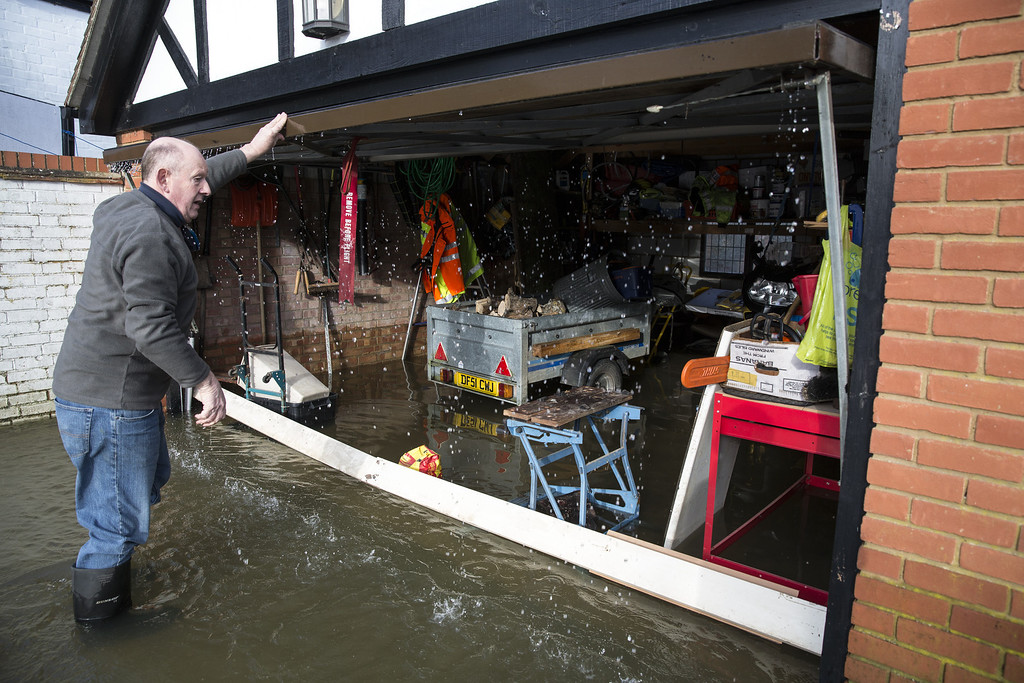 . A man examines his flooded garage, near the river Thames on February 13, 2014 in Wargrave, England. (Photo by Oli Scarff/Getty Images)