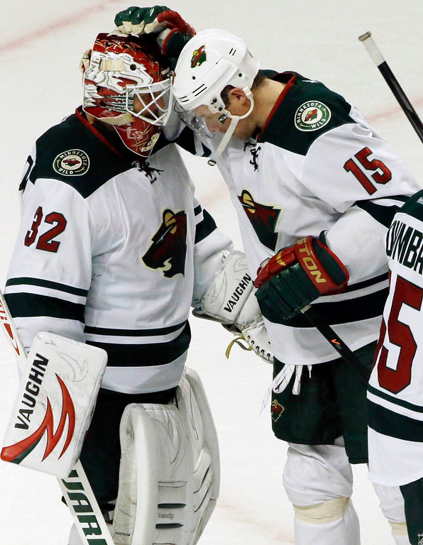 . Minnesota Wild goalie Niklas Backstrom (32) celebrates with Dany Heatley (15) after the Wild defeated the Chicago Blackhawks 5-3. (AP Photo/Nam Y. Huh)