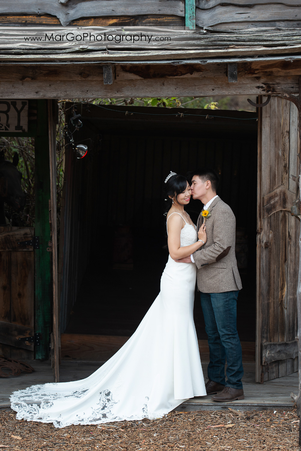 full body portrait of the bride and groom kissing her cheek at Long Branch Saloon & Farms in Half Moon Bay