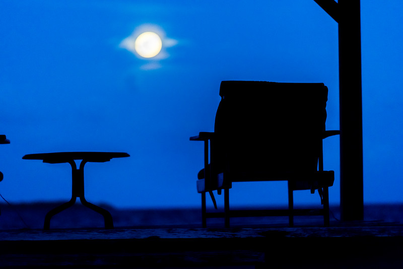 Silhouette of chair and table with moon glowing in the sky, Turneffe Island, Belize
