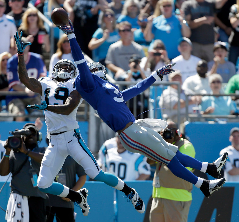 . New York Giants\' Aaron Ross, right, knocks the ball away from Carolina Panthers\' Ted Ginn, left, during the first half of an NFL football game in Charlotte, N.C., Sunday, Sept. 22, 2013. (AP Photo/Bob Leverone)