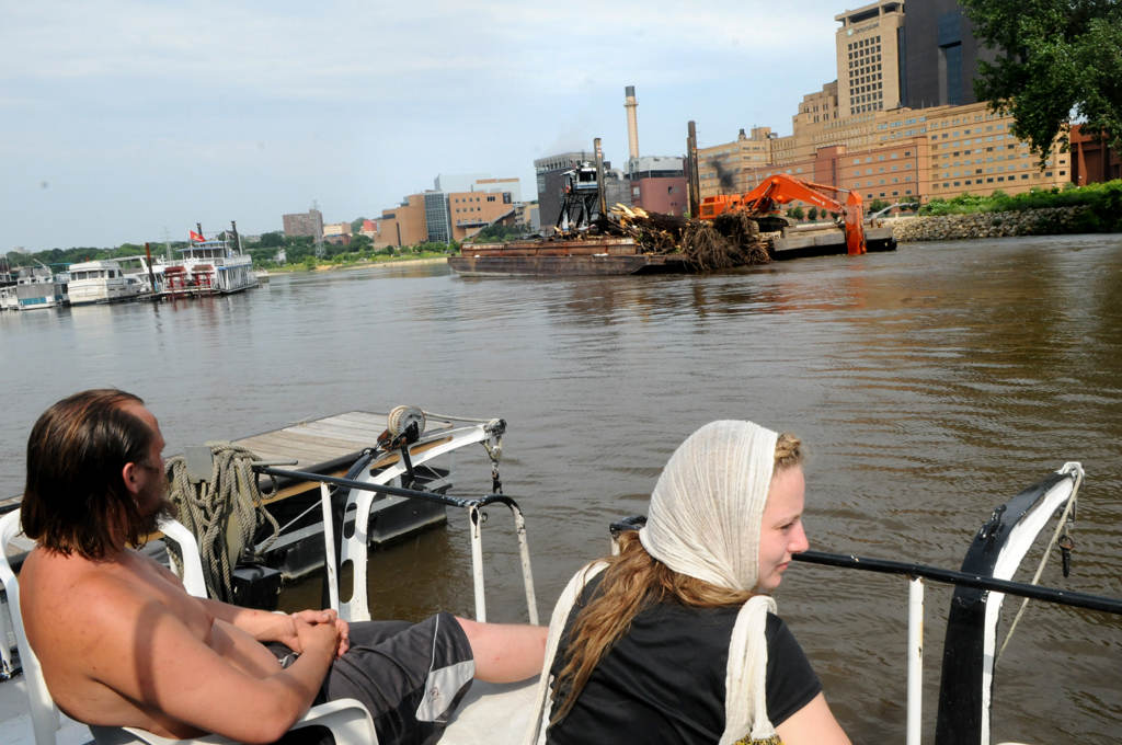 . Emily Ingvalsen, right, and her husband, Brandon Dorweiler, sit in chairs on their houseboat and watch a barge leave with debris just collected from the logjam.  (Pioneer Press: Jean Pieri)