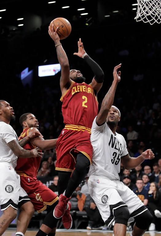 . Cleveland Cavaliers\' Kyrie Irving (2) drives past Brooklyn Nets\' Trevor Booker (35) as teammate Tristan Thompson, left, watches during the first half of an NBA basketball game Friday, Jan. 6, 2017, in New York. (AP Photo/Frank Franklin II)