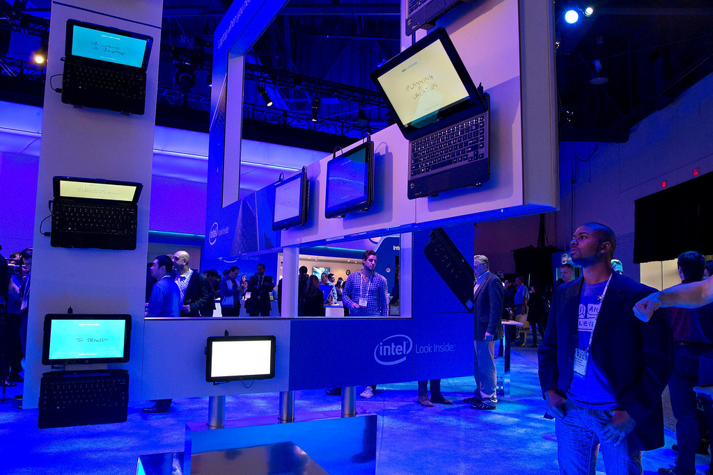 . Trade show attendees examine a display of various 2-in-1 laptops at the Intel booth at the International Consumer Electronics Show, Wednesday, Jan. 8, 2014, in Las Vegas. (AP Photo/Julie Jacobson)