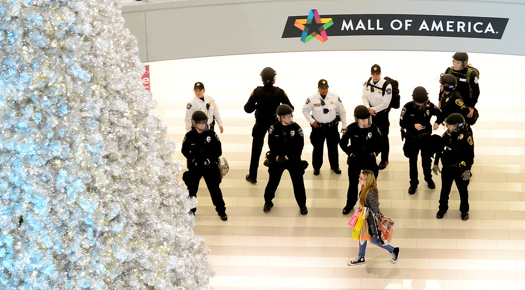 . A shopper walks past a group of police in the rotunda area during the Black Lives Matter demonstration at the Mall of America on Dec. 20, 2014. (Pioneer Press: John Autey)