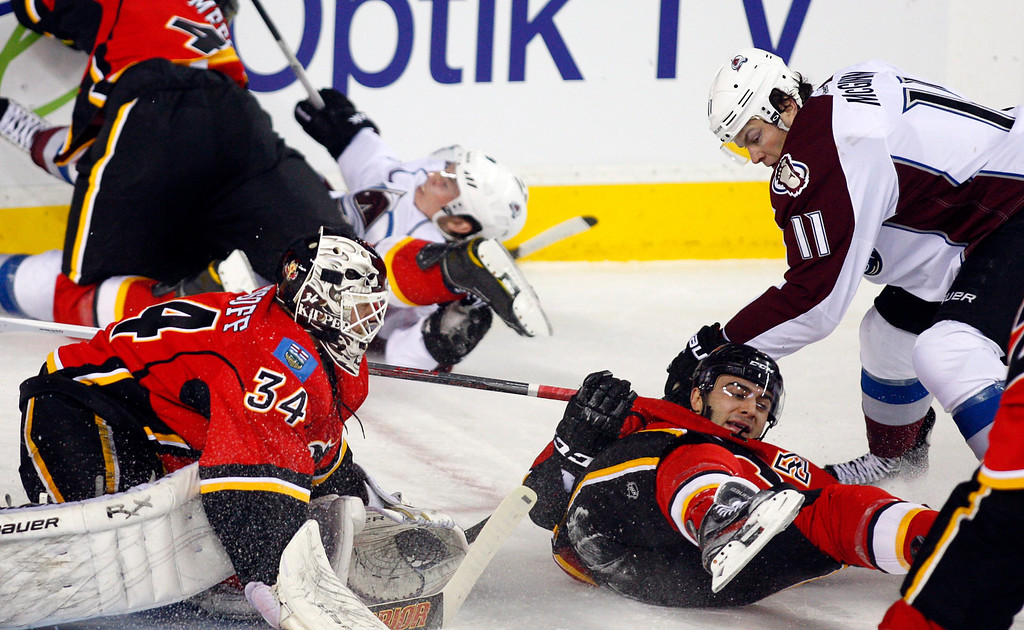. Colorado Avalanche\'s Jamie McGinn, right, knocks Calgary Flames\' Mark Giordano, center, to the ice as goalie Miikka Kiprusoff, from Finland, watches during the first period of an NHL hockey game Thursday, Jan. 31, 2013, in Calgary, Alberta. (AP photo/The Canadian Press, Jeff McIntosh)