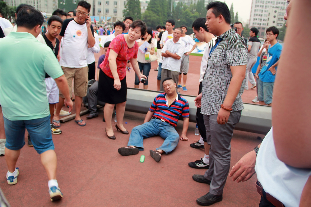 . People gather around a man injured in a crush as David Beckham arrives at Tongji University on June 20, 2013 in Shanghai, China. The stampede is reported to have left five people injured and hospitalised. (Photo by Getty Images)