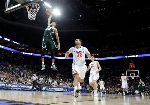 . Michigan State\'s Travis Trice (20) goes up to dunk against Virginia during the first half of an NCAA tournament college basketball game in the Round of 32 in Charlotte, N.C., Sunday, March 22, 2015. (AP Photo/Gerald Herbert)