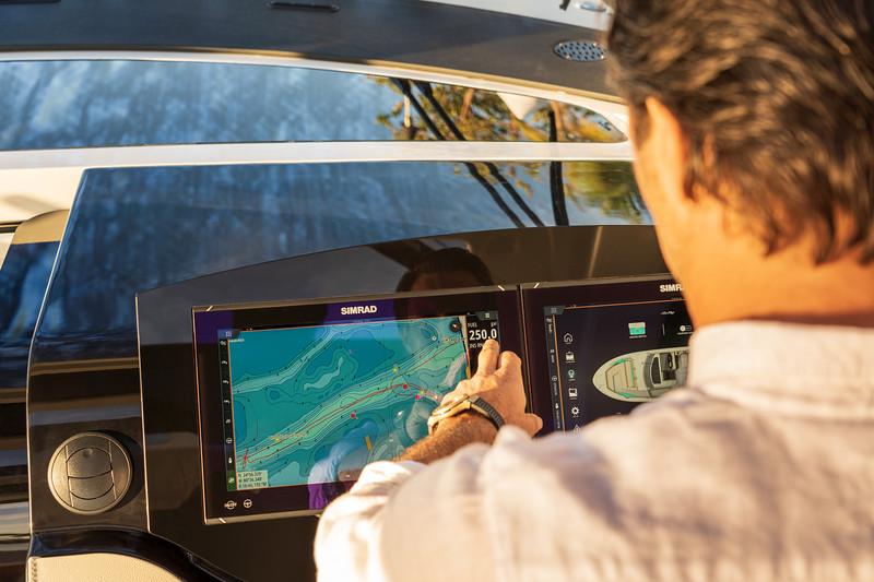 2021-Sundancer-370-Outboard-DAO370-lifestyle-hand-man-helm-dash-Simrad-06631.jpg