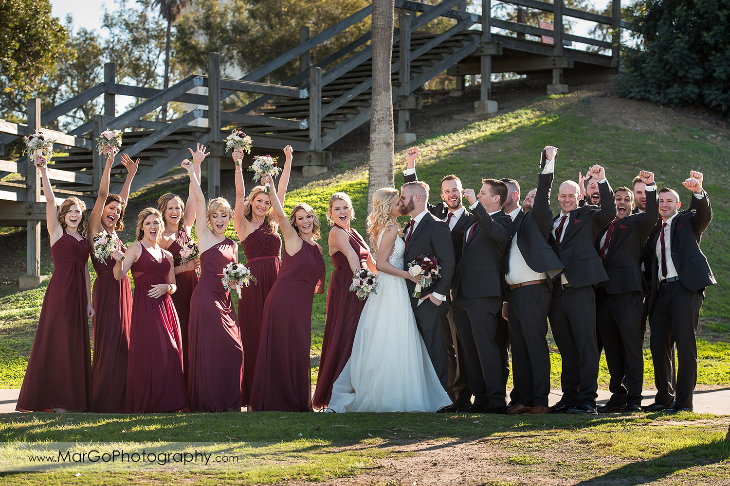 bride and groom kissing with cheering bridal party at San Diego Mission Bay Park