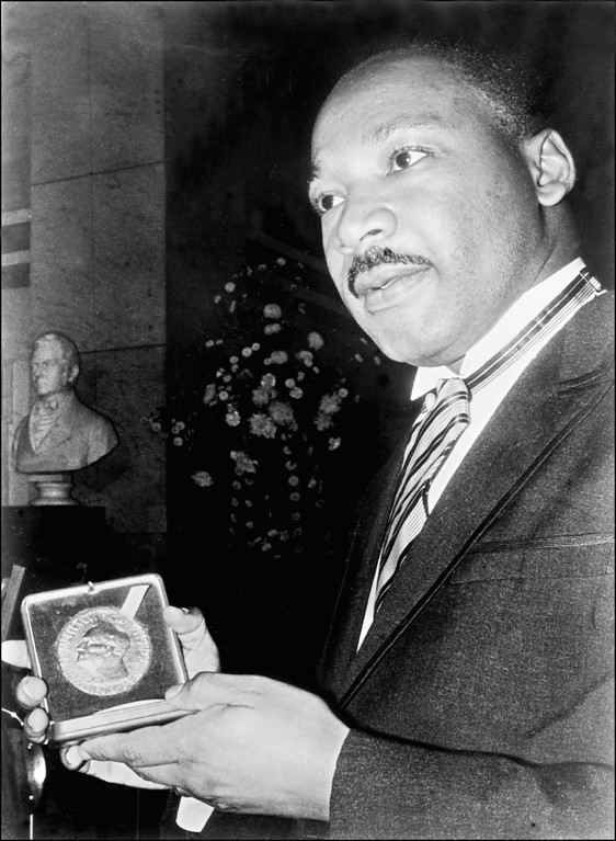 . OSLO, NORWAY:  US civil rights leader Martin Luther King, displays 10 December 1964 in Oslo, his Nobel Peace Prize medal. (Photo credit should read AFP/Getty Images)