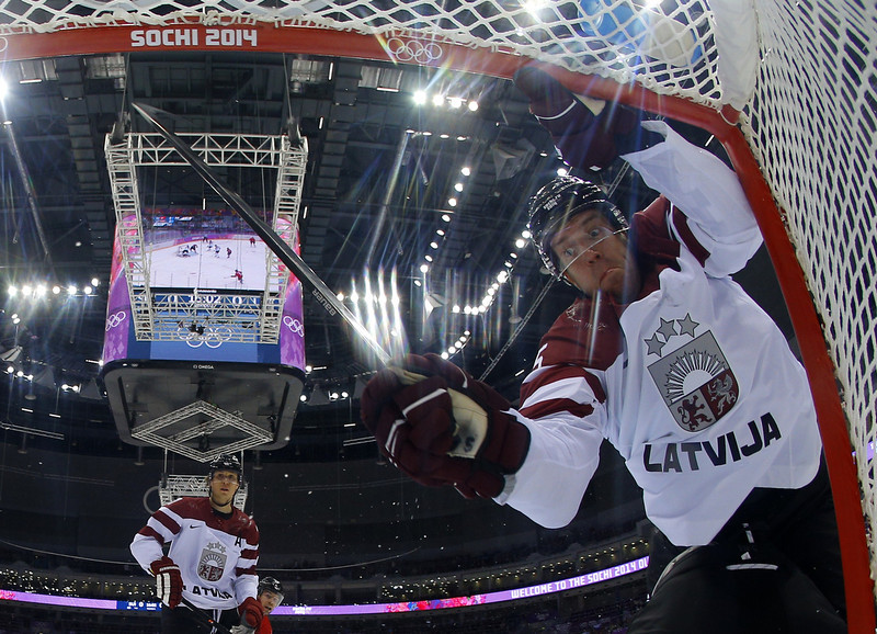. Latvia\'s Janis Sprukts (top R) falls over Latvia\'s goalkeeper Edgars Masalskis (unseen)  during the Men\'s Ice Hockey Play-offs Switzerland vs Latvia at the Bolshoy Ice Dome during the Sochi Winter Olympics on February 18, 2014.  (MARK BLINCH/AFP/Getty Images)
