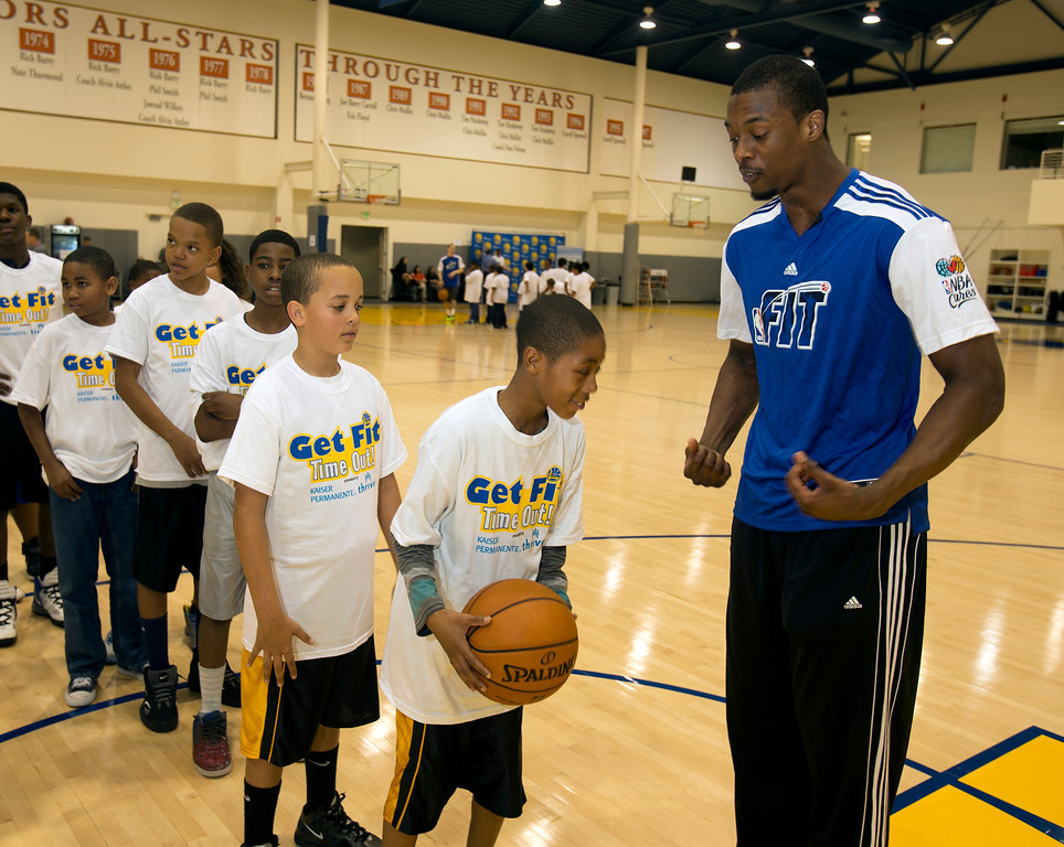 . Golden State Warriors forward Harrison Barnes, right, demonstrates the proper shooting technique to a group of children participating in a basketball clinic at the Warriors practice facility in downtown Oakland, Calif., Wednesday, Jan. 30, 2013. The Warriors and Kaiser Permanente hosted the event as part of the NBA FIT Live Healthy Week. (D. Ross Cameron/Staff)