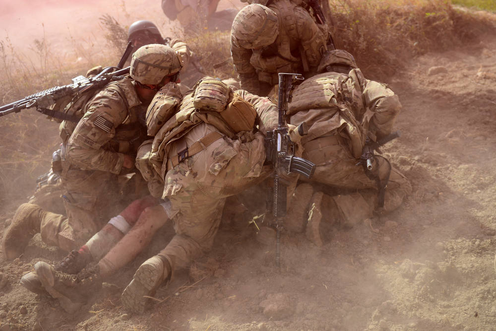 Description of . US Army soldiers attached to 2nd platoon, C troop, 1st Squadron (Airborne), 91st U.S Cavalry Regiment, 173rd Airborne Brigade Combat Team operating under NATO sponsored International Security Assistance Force (ISAF) protect a wounded comrade from dust and smoke flares after an Improvised Explosive Device (IED) blast during a patrol near Baraki Barak base in Logar Province on October 13, 2012. The soldier, 21 year-old Private Ryan Thomas from Oklahoma suffered soft tissue damage and after surgery in Afghanistan was scheduled to be evacuated to Germany.    After 11 years of war, 2,135 US soldiers dead, their Afghan colleagues turning on them, and widespread predictions the conflict will end in failure, coalition forces could be forgiven for suffering a dip in morale. But commanders and soldiers on the ground insist the challenges are bringing them closer together, even if the outcome of the war is uncertain and the perception of what constitutes success has changed.   AFP PHOTO/ Munir uz  ZAMAN/AFP/Getty Images
