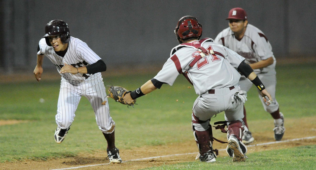 . 03-21-2013--(LANG Staff Photo by Sean Hiller)- Paramount hosts Downey in Thursday\'s high school baseball game. Paramount\'s Frankie Valenzuela tries to out run Downey\'s catcher Juan Gonzalez before finally getting tagged out by Downey\'s pitcher Richard Gomez, not pictured.
