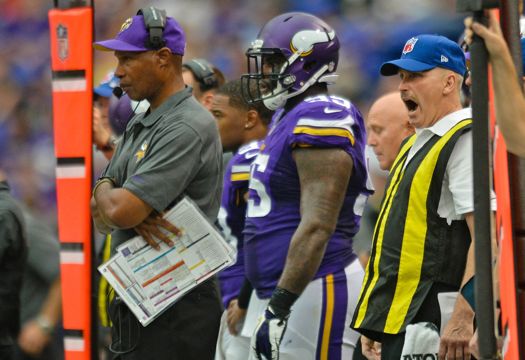 . Vikings head coach Leslie Frazier watches from the sidelines with a sleepy sideline official during the second half. (Pioneer Press: Ben Garvin)