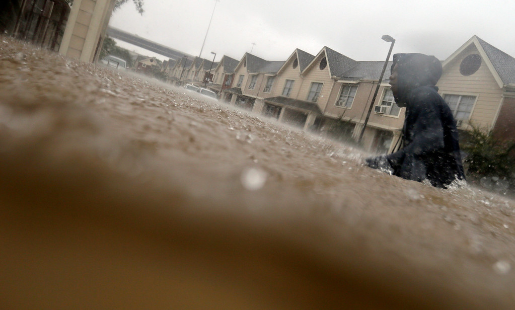 . A child makes his way through floodwaters from Tropical Storm Harvey while checking on neighbors at his apartment complex in Houston, Sunday, Aug. 27, 2017. The remnants of Hurricane Harvey sent devastating floods pouring into Houston Sunday as rising water chased thousands of people to rooftops or higher ground. (AP Photo/LM Otero)