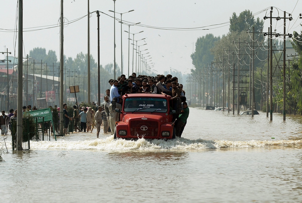 . Kashmiri people travel on a truck along a flooded street in Srinagar on September 10, 2014.    AFP PHOTO/ PUNIT  PARANJPE/AFP/Getty Images