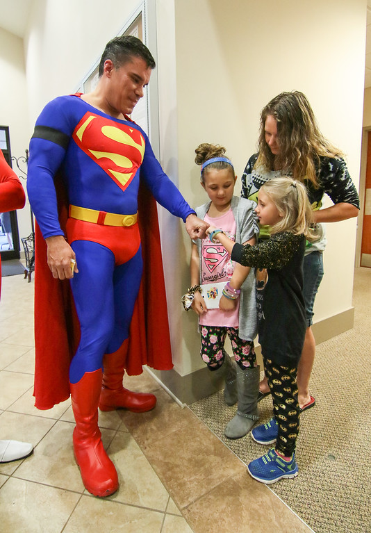 . Zowie Sanders, gives a fist bump to John Suber, left, of Greenville, dressed as Superman, with her sister Lindsey Sanders, center, and their mother Brooke Starks, right, of Townville, during a wake service for Jacob Hall at Oakdale Baptist Church in Townville, S.C., Wednesday, Oct. 4, 2016. Jacob, a classmate and a teacher were shot last Wednesday as they left for recess. Authorities say the suspect, a 14-year-old boy, had shot his father to death before driving to Townville Elementary. The other student and teacher were treated and released from a hospital that day. (Ken Ruinard/The Independent-Mail via AP, Pool)