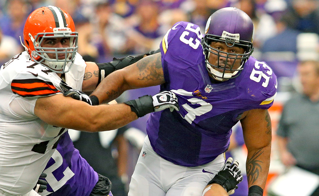 . Minnesota defensive tackle Kevin Williams is slowed by Browns offensive lineman John Greco during the first half of their game. Williams set a Vikings franchise record, playing in his 158th game.  (Photo by Adam Bettcher/Getty Images)