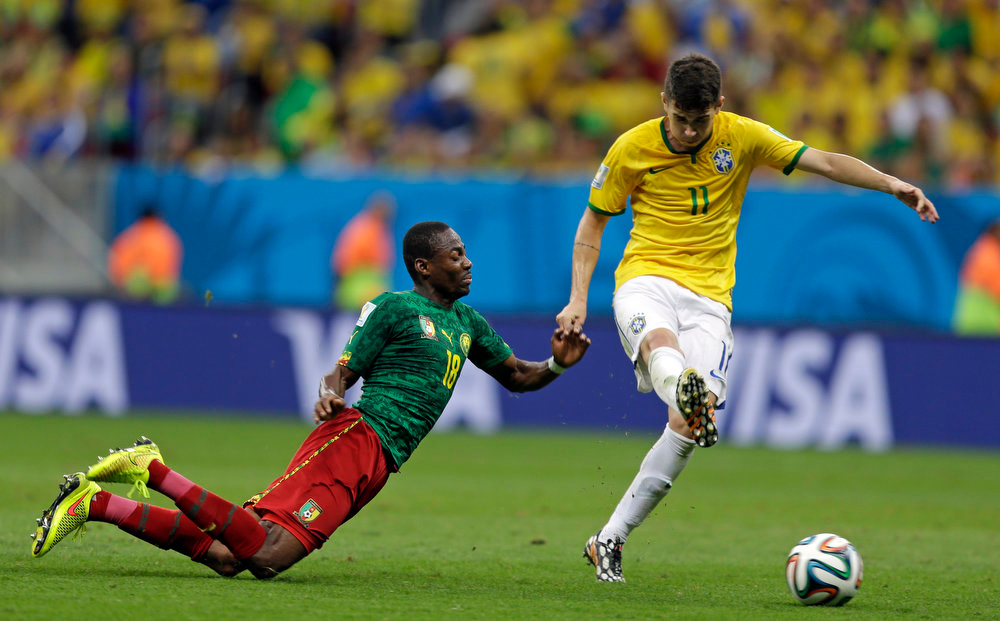 . Cameroon\'s Eyong Enoh, left, falls beside Brazil\'s Oscar during the group A World Cup soccer match between Cameroon and Brazil at the Estadio Nacional in Brasilia, Brazil, Monday, June 23, 2014. (AP Photo/Andre Penner)