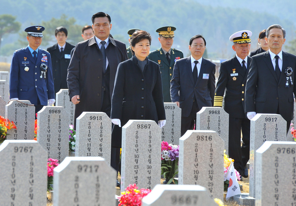 . South Korean President Park Geun-hye, center, walks through gravestones for South Korean sailors killed in a sunken war ship, at a cemetery in Daejeon, South Korea, Tuesday, March 26, 2013. An explosion ripped apart the 1,200-ton warship, killing 46 sailors near the maritime border with North Korea in 2010. South Korea marks three years from the incident on March 26. (AP Photo/Kim Jae-hwan, Pool)