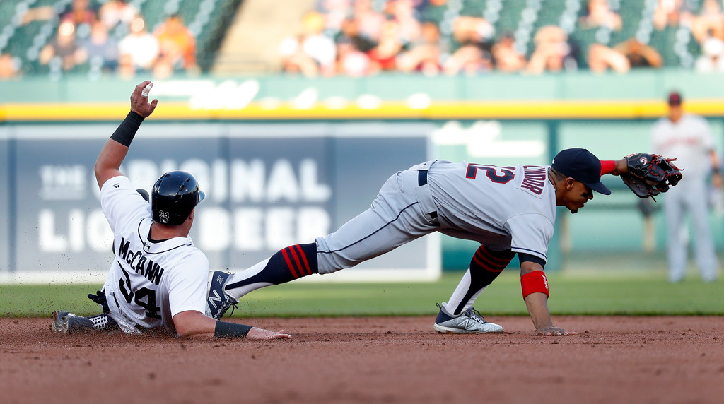 . Cleveland Indians shortstop Francisco Lindor (12) stretches to collect the ball for an out on Detroit Tigers\' James McCann (34) at second base in the second inning of a baseball game in Detroit, Monday, May 14, 2018. (AP Photo/Paul Sancya)