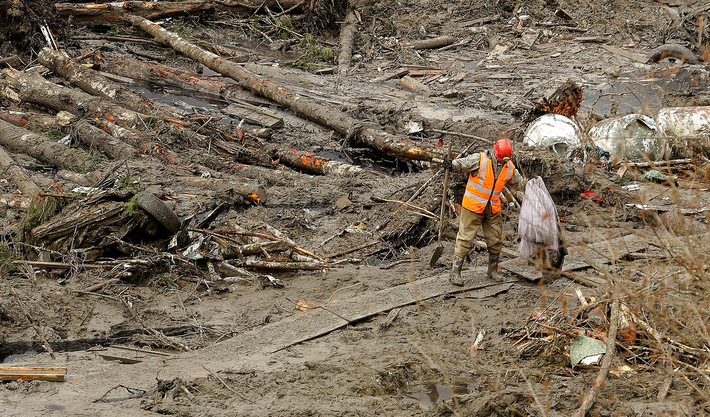 . A worker carries a recovered item along a plywood walkway through other debris, Sunday, March 30, 2014, as search work continues at the site of the massive mudslide that struck the community of Oso,Wash. on March 22, 2014. (AP Photo/Ted S. Warren)