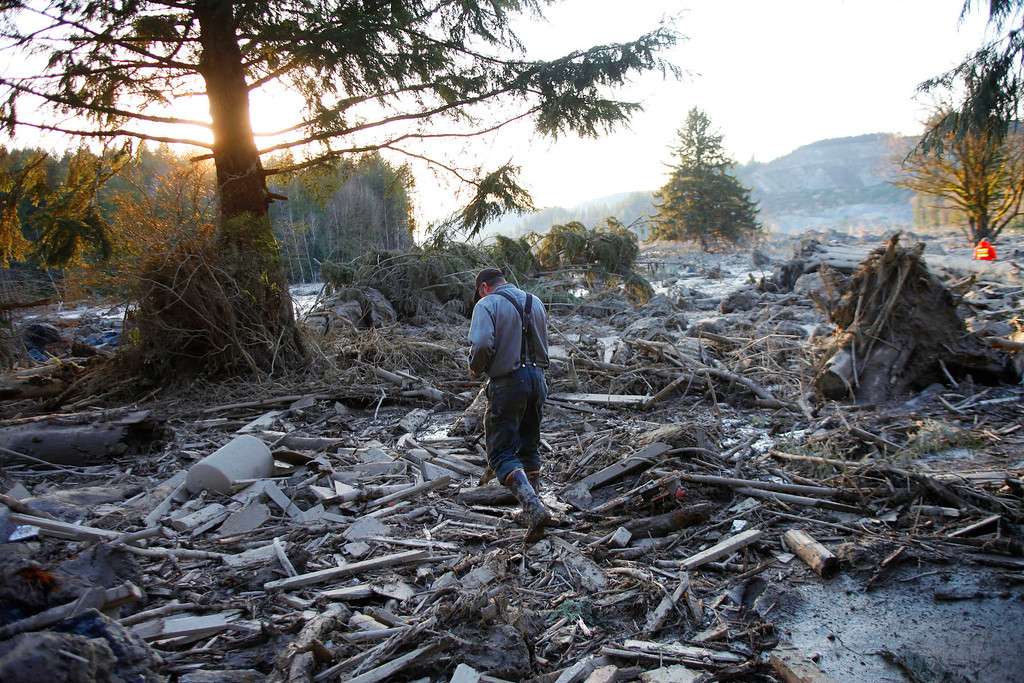 . Steve Skaglund walks across the rubble on the east side of Saturday\'s fatal mudslide near Oso, Wash., Sunday, March 23, 2014. (AP Photo /The Herald, Genna Martin)