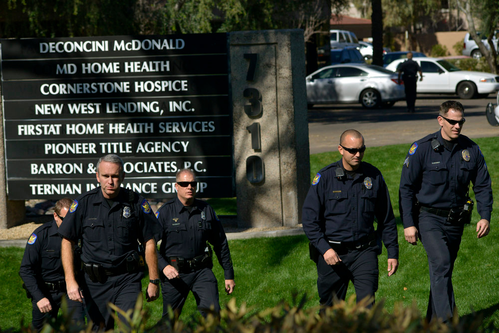 . Police officers leave an office building after a shooting at the building in Phoenix on Wednesday, Jan. 30, 2013. A gunman opened fire at the Phoenix office building, wounding three people, one of them critically, authorities said. Police were searching for the shooter. (AP Photo/Patrick Sison)