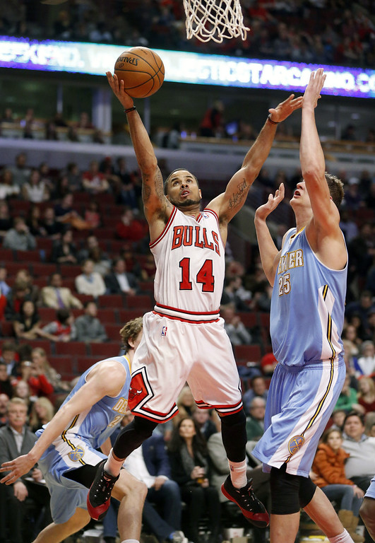 . Chicago Bulls guard D.J. Augustin (14) shoots past Denver Nuggets center Timofey Mozgov, right, during the second half of an NBA basketball game Friday, Feb. 21, 2014, in Chicago. The Bulls won 117-89. (AP Photo/Charles Rex Arbogast)