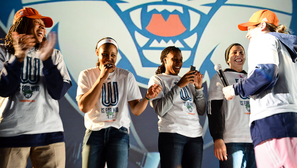 . Lynx players (from left) Seimone Augustus, Maya Moore, Rebekkah Brunson and Janel McCarville laugh after Lindsay Whalen, right, spoke to the crowd during the team\'s WNBA championship pep rally.  (Pioneer Press: Ben Garvin)