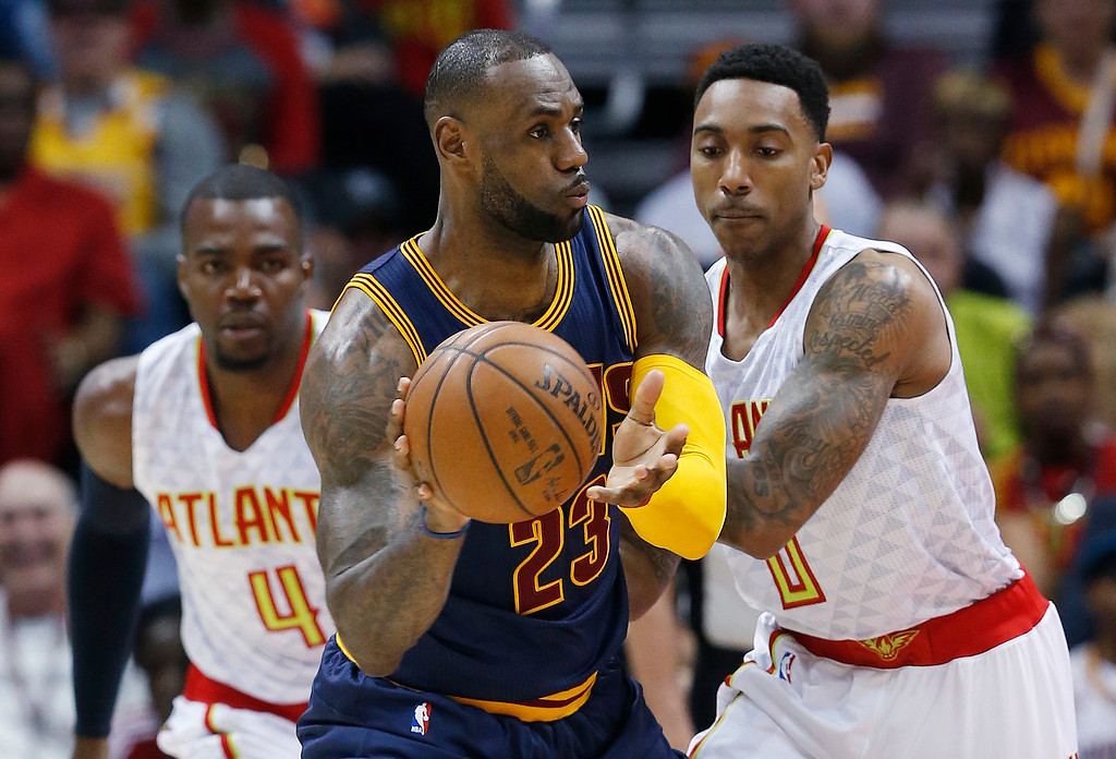 . Cleveland Cavaliers forward LeBron James (23) looks to pass against Atlanta Hawks\' Jeff Teague (0) and Paul Millsap (4) during Game 4 of the second-round NBA basketball playoff series, Sunday, May 8, 2016, in Atlanta. (AP Photo/John Bazemore)