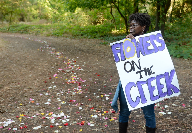 """Beverlee Allen of Chico holds a sign guiding attendees to the Campfire Council Ring during the """"Flowers on the Creek"""" Domestic violence victims remembrance at the One Mile Recreation Area of Bidwell Park in Chico, Calif. Thursday, Oct. 4, 2018.   (Bill Husa -- Enterprise-Record)"""